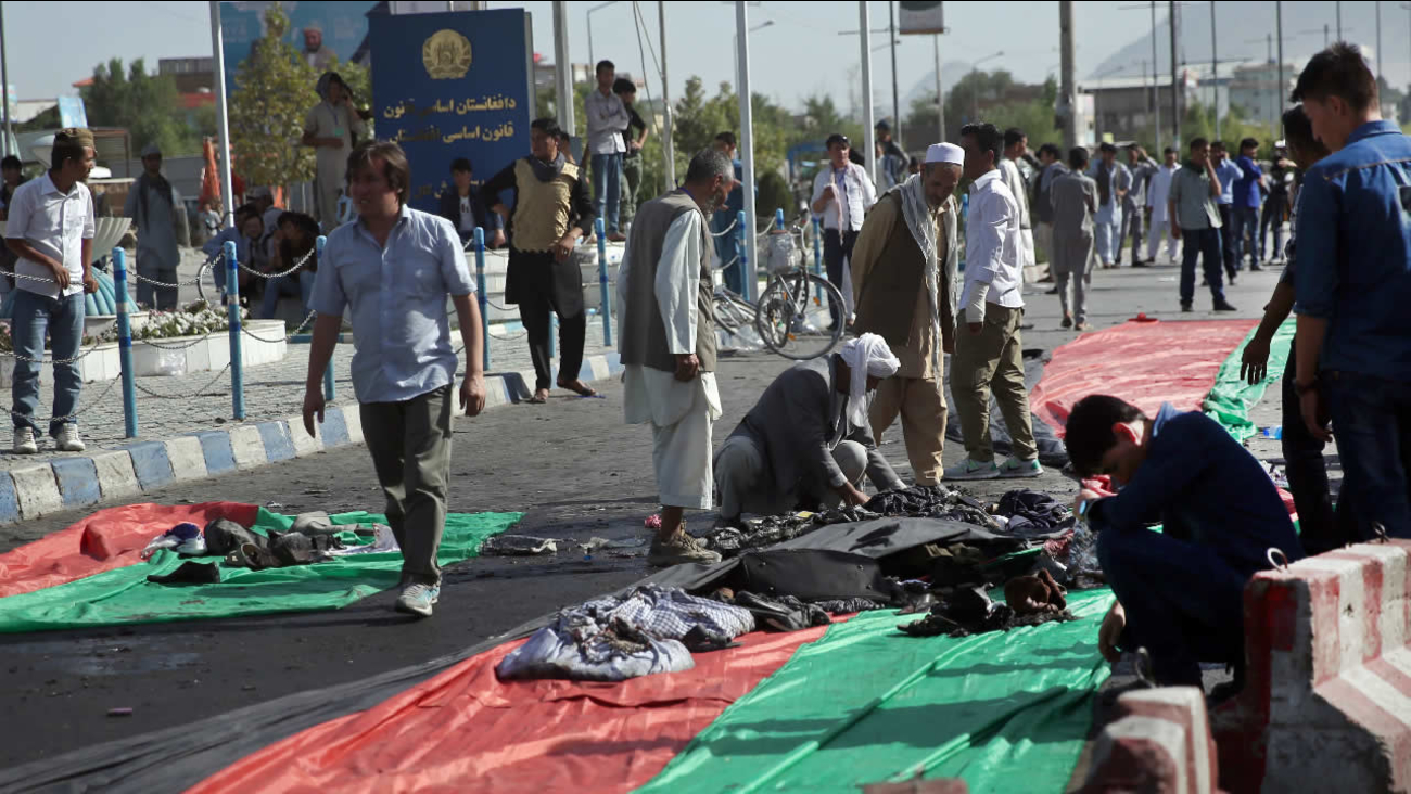 Afghan men gather property, on banners in the colors of the Afghan flag, that was left behind after a deadly explosion struck a protest march by ethnic Hazaras, in Kabul, Afghanistan, Saturday, July 23, 2016.