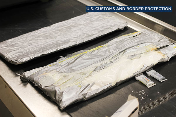 U.S. Customs and Border Protection officers display crystal meth found hidden in a woman's luggage at Los Angeles International Airport on July 18, 2016.