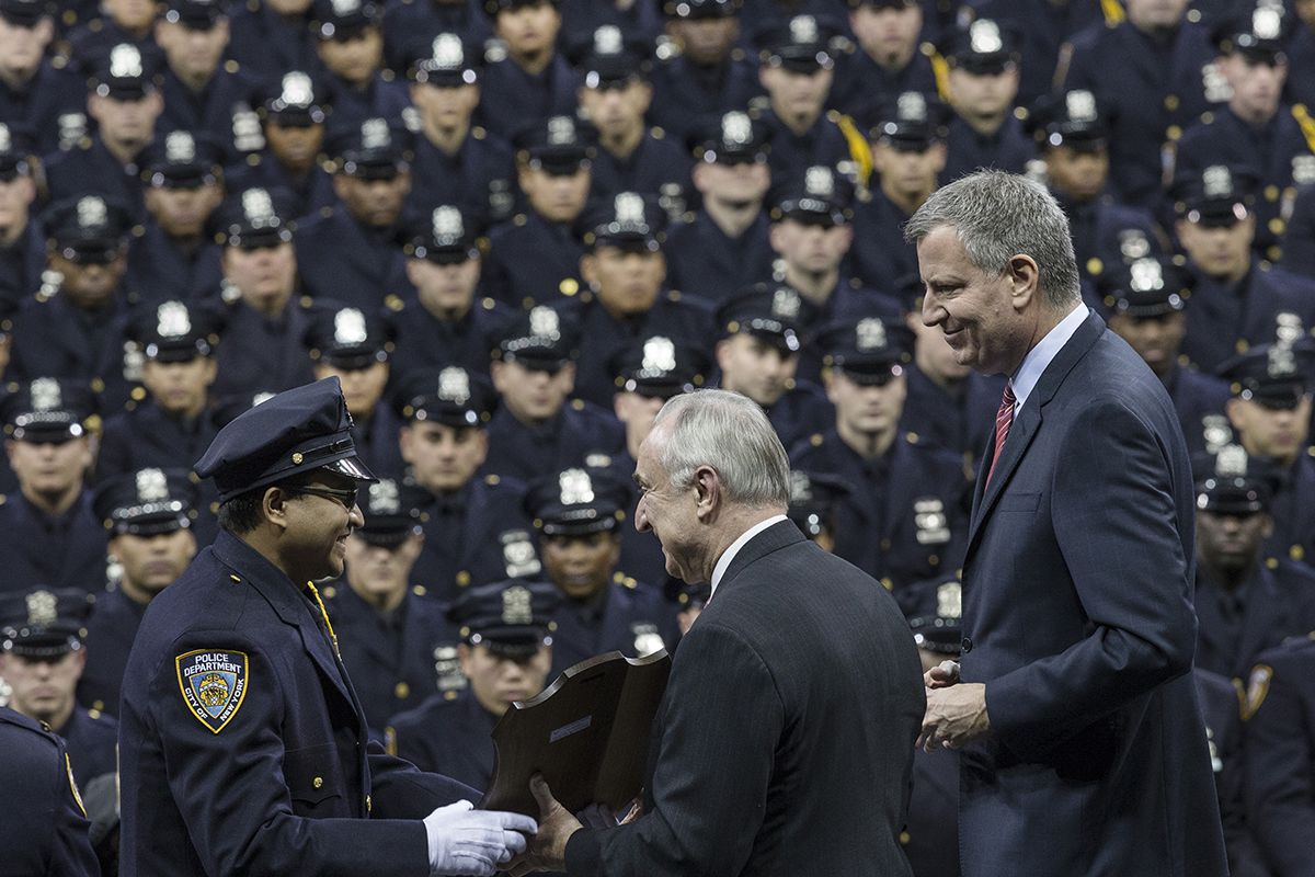 "<div class=""meta image-caption""><div class=""origin-logo origin-image ap""><span>AP</span></div><span class=""caption-text"">NYC Mayor Bill de Blasio, right, and police commissioner Bill Bratton, center, present an award to a recruit during a NY Police Academy graduation ceremony, Monday, Dec. 29, 2014. (AP Photo/John Minchillo)</span></div>"