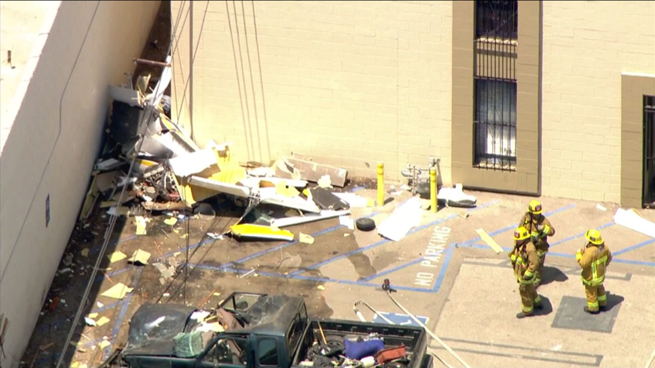 Emergency personnel investigate the scene in Van Nuys, where a small plane crashed into a building on Tuesday, Aug. 2, 2016.