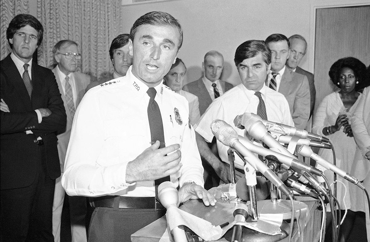 "<div class=""meta image-caption""><div class=""origin-logo origin-image ap""><span>AP</span></div><span class=""caption-text"">Mass. Bay Transportation Authority Police Chief William J. Bratton, left, answers questions at a news conference at the McCormack Building in Boston on Wednesday, July 20, 1983. (AP Photo)</span></div>"