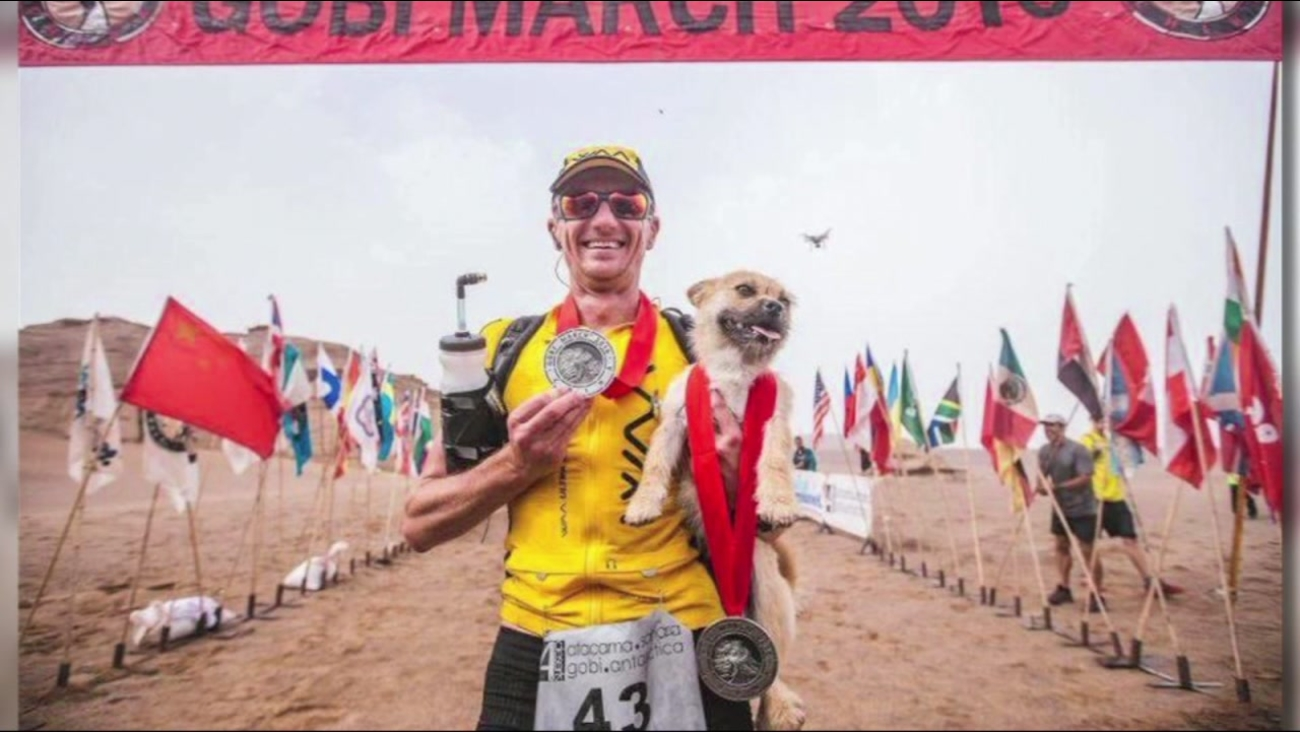 "Dion Leonard poses with the dog he nicknamed ""Gobi"" after who ran with him for 77 miles in a race across the Gobi Dessert."