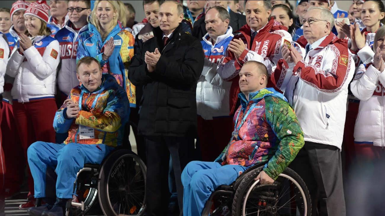 In this photo taken Thursday, March 6, 2014, Russian President Vladimir Putin, center, greets athletes in Krasnaya Polyana, Russia.