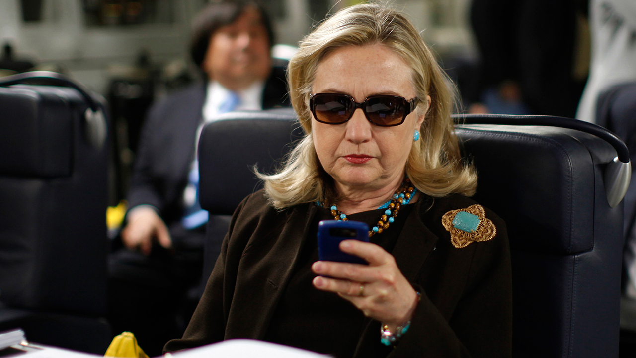 FILE - In this Oct. 18, 2011, file photo, then-Secretary of State Hillary Rodham Clinton checks her Blackberry from a desk inside a C-17 military plane
