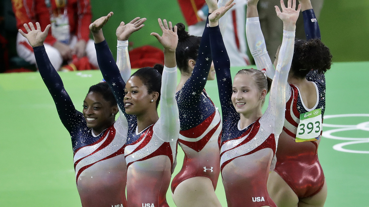 U.S. gymnasts, left to right, Simone Biles, Gabrielle Douglas, Aly Raisman, Madison Kocian, and Lauren Hernandez wave to the audience at the end of the artistic gymnastics