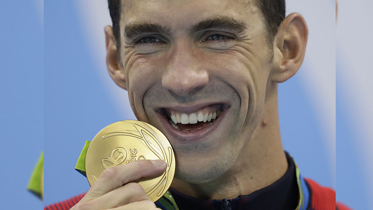 Michael Phelps has tears of joy in his eyes as he displays his 20th gold medal, only a short time before also picking up his 21st in Rio de Janeiro.