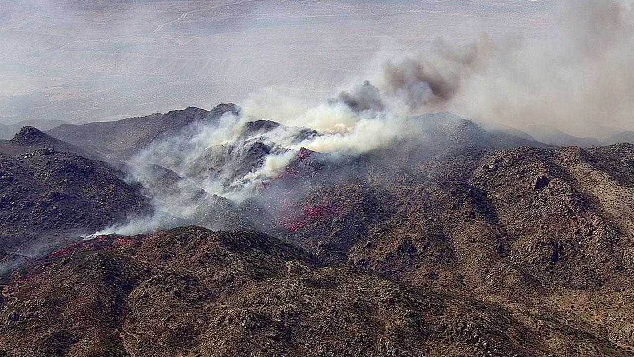 The Pilot Fire in the San Bernardino hillsides burns through dry brush, sending up plumes of smoke.