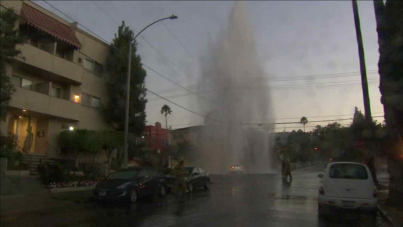 Firefighters respond to the scene of a crash that led to water shooting up from a fire hydrant in Hollywood on Sunday, Aug. 14, 2016.