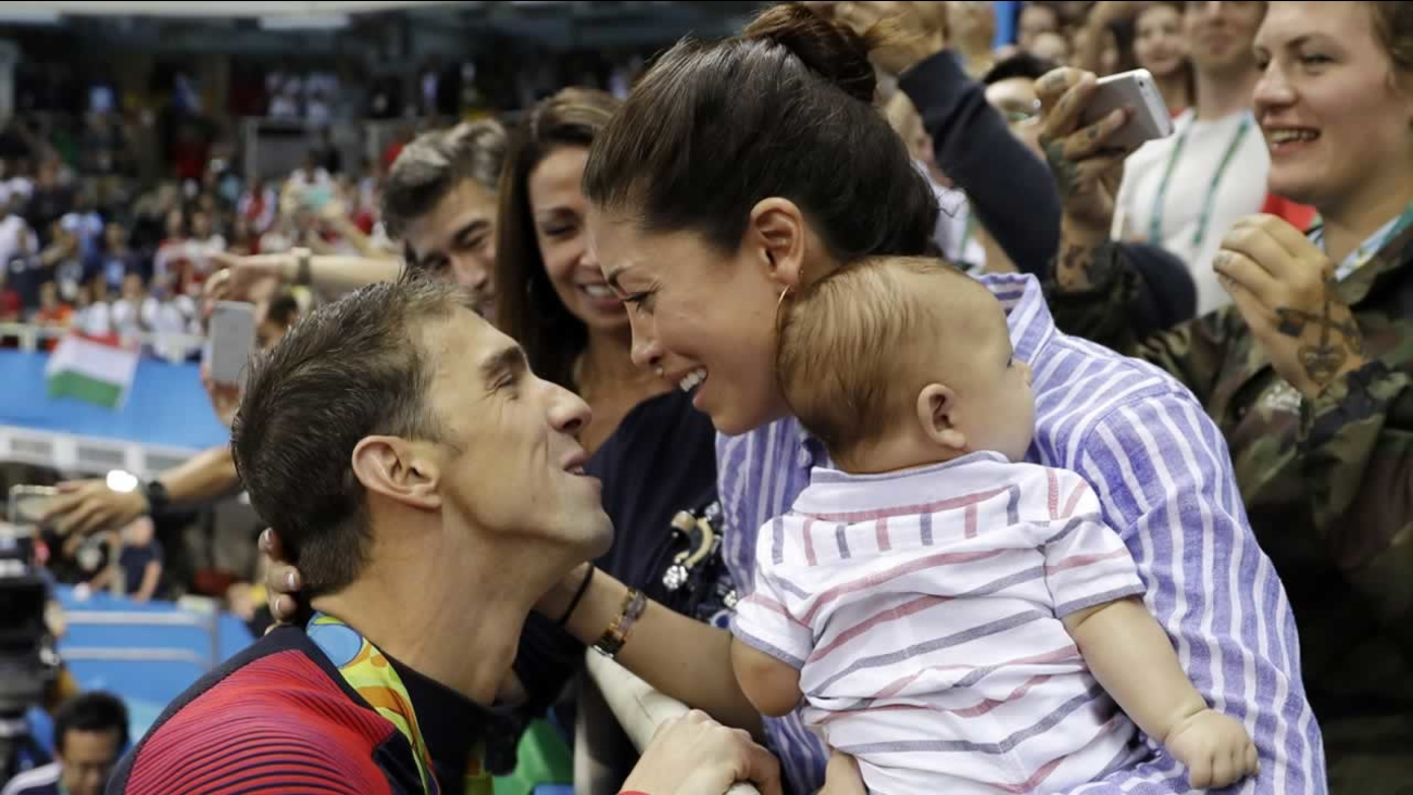 Michael Phelps celebrates winning his gold medal in the men's 200-meter butterfly with his fiance Nicole Johnson and baby Boomer, Tuesday, Aug. 9, 2016, in Rio de Janeiro, Brazil.