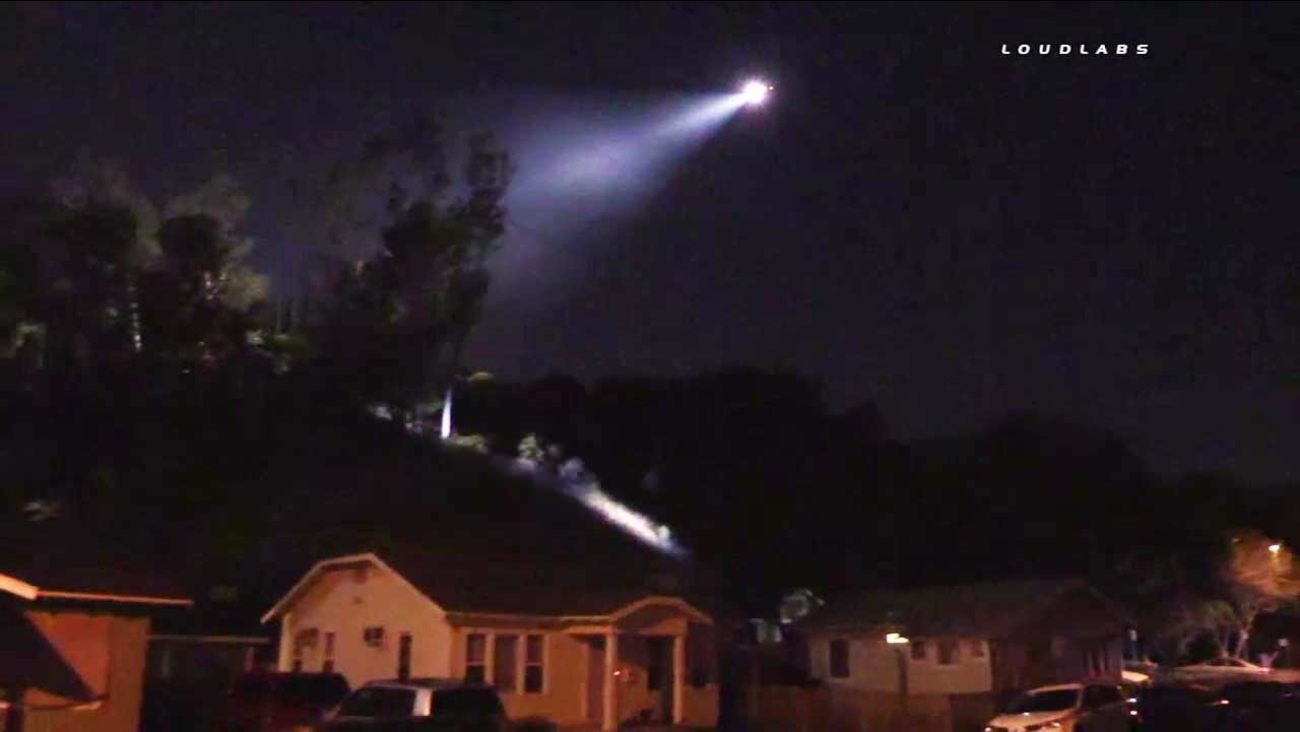 A law enforcement aircraft shines a spotlight in the Eagle Rock area after a shooting suspect bailed on foot following a police chase on Thursday, Aug. 18, 2016.
