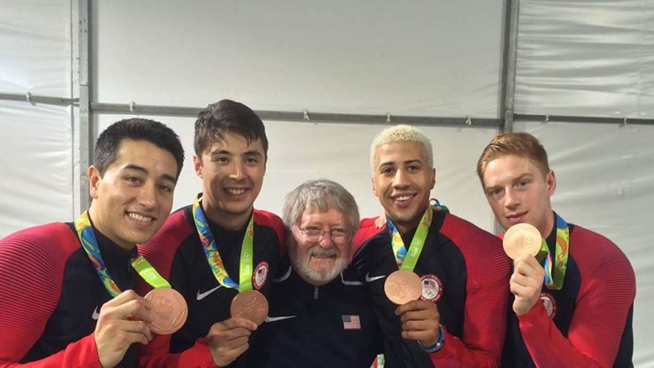 The image shows Matthew Porter (center) with the bronze-medal-winning U.S. men's fencing team.