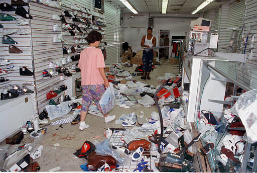 "<div class=""meta image-caption""><div class=""origin-logo origin-image none""><span>none</span></div><span class=""caption-text"">Employees clean up a sneaker store at the corner of Union Street and Utica Avenue that was vandalized during violence between residents and police in Crown Heights, Aug. 21, 1991. (AP Photo/Mario Cabrera)</span></div>"