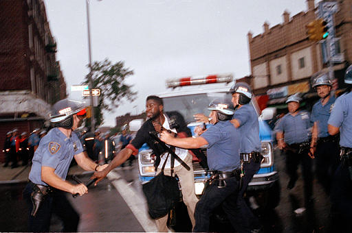 """<div class=""""meta image-caption""""><div class=""""origin-logo origin-image none""""><span>none</span></div><span class=""""caption-text"""">Police arrest a man who was taking pictures during violence between residents and police in the Crown Heights section of Brooklyn, N.Y., Aug. 21, 1991. (AP Photo/David Burns)</span></div>"""