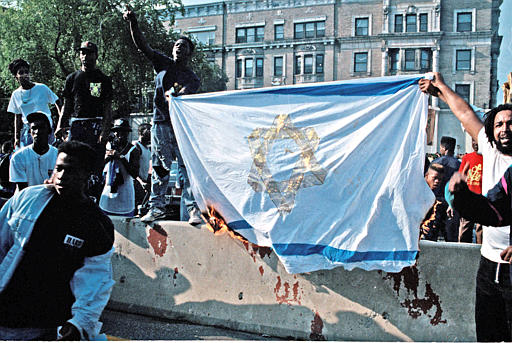 "<div class=""meta image-caption""><div class=""origin-logo origin-image none""><span>none</span></div><span class=""caption-text"">Demonstrators in the Crown Heights section of the Brooklyn borough of New York burn a makeshift Israeli flag during a protest march, Aug. 21, 1991. (AP Photo/Joe Major)</span></div>"