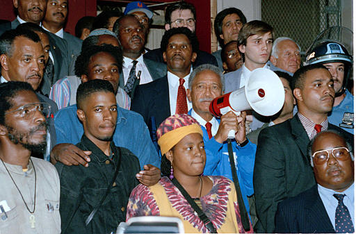 """<div class=""""meta image-caption""""><div class=""""origin-logo origin-image none""""><span>none</span></div><span class=""""caption-text"""">Mayor David Dinkins, with bullhorn, appeals to an angry crowd gathered at the home of 7-year-old Gavin Cato, whose death sparked rioting in Crown Heights, Aug. 22, 1991. (AP Photo/Joe Major)</span></div>"""