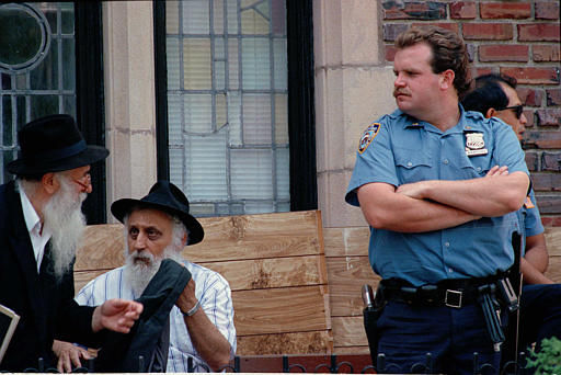 """<div class=""""meta image-caption""""><div class=""""origin-logo origin-image none""""><span>none</span></div><span class=""""caption-text"""">A New York City police officer stands guard as two Hasidic Jewish men go about their business in the Crown Heights neighborhood of Brooklyn, N.Y., Aug. 23, 1991. (AP)</span></div>"""