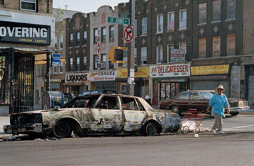 """<div class=""""meta image-caption""""><div class=""""origin-logo origin-image none""""><span>none</span></div><span class=""""caption-text"""">A woman passes a fire-bombed car as she crosses St. Johns Place on Utica Avenue in the Crown Heights sectioin of Brooklyn, Aug. 22, 1991. (AP Photo/David Cantor)</span></div>"""