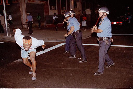 """<div class=""""meta image-caption""""><div class=""""origin-logo origin-image none""""><span>none</span></div><span class=""""caption-text"""">A protester in a crowd demanding that police leave Crown Heights runs for safety after being struck by police as the crowd marched down Utica Avenue, Aug. 23, 1991. (AP Photo/Bebeto Matthew)</span></div>"""