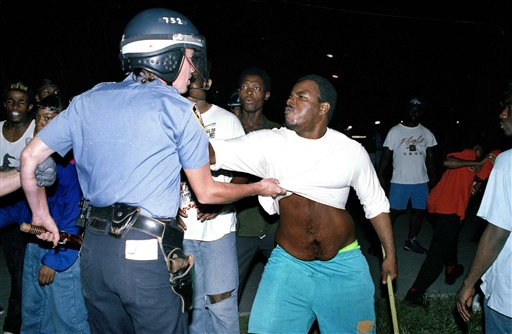 "<div class=""meta image-caption""><div class=""origin-logo origin-image none""><span>none</span></div><span class=""caption-text"">A police officer in riot gear and a protester tug at each other during the fourth consecutive night of violence between police and residents in Crown Heights, Aug. 22, 1991. (AP Photo/Joe Major)</span></div>"