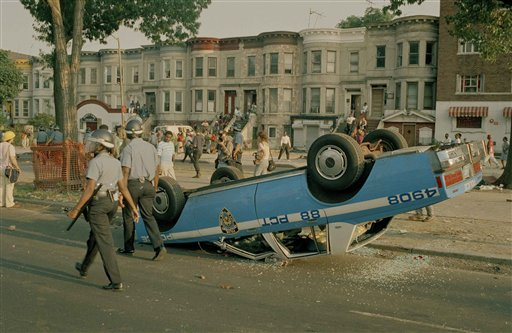 """<div class=""""meta image-caption""""><div class=""""origin-logo origin-image none""""><span>none</span></div><span class=""""caption-text"""">Police in riot gear walk past a police car that was overturned by rioters in the Crown Heights section of Brooklyn, New York, Aug. 21, 1991. (AP Photo/David Burns)</span></div>"""
