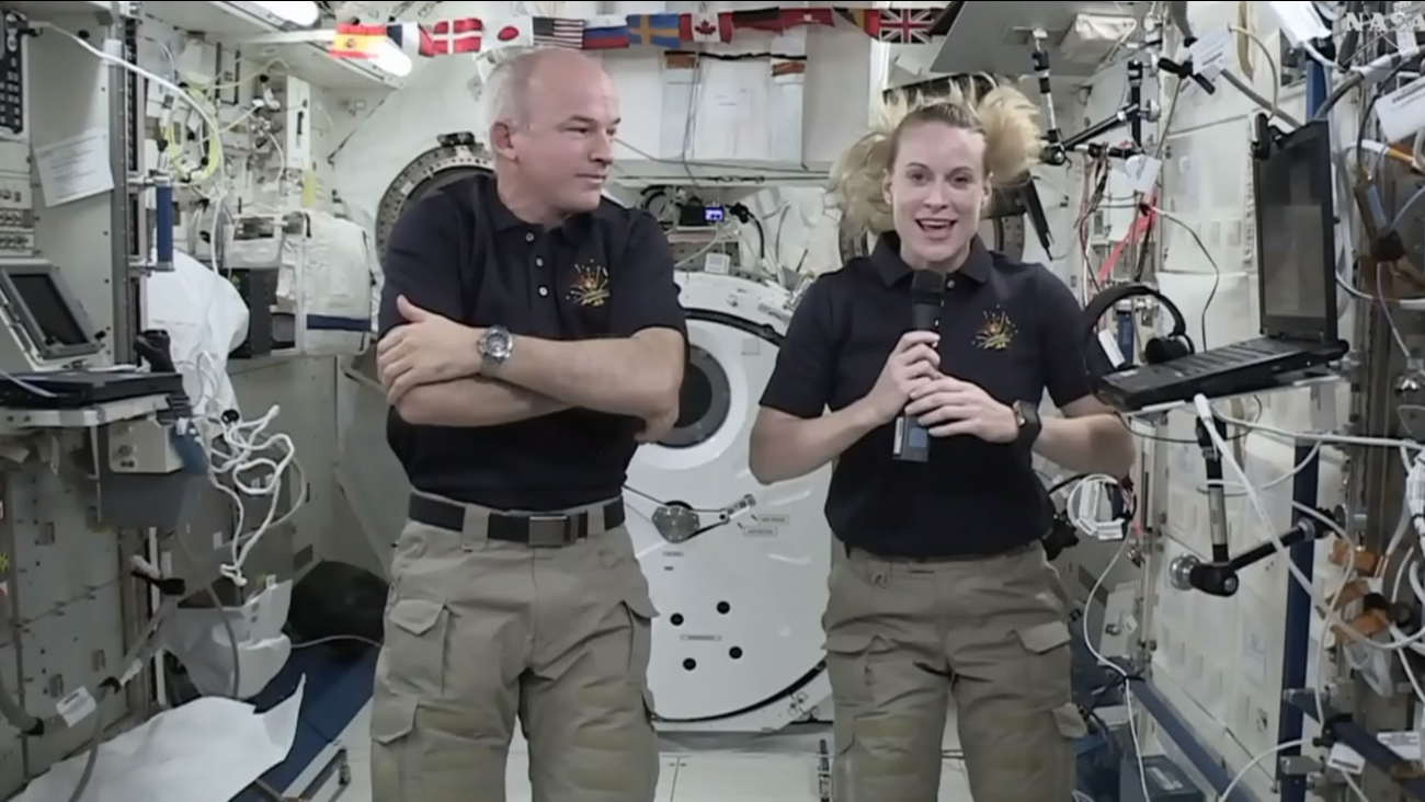Astronaut Kate Rubins, right, speaks during an interview aboard the International Space Station on Wednesday, July 13, 2016. At left is Expedition 48 Commander Jeff Williams. (NASA via AP)
