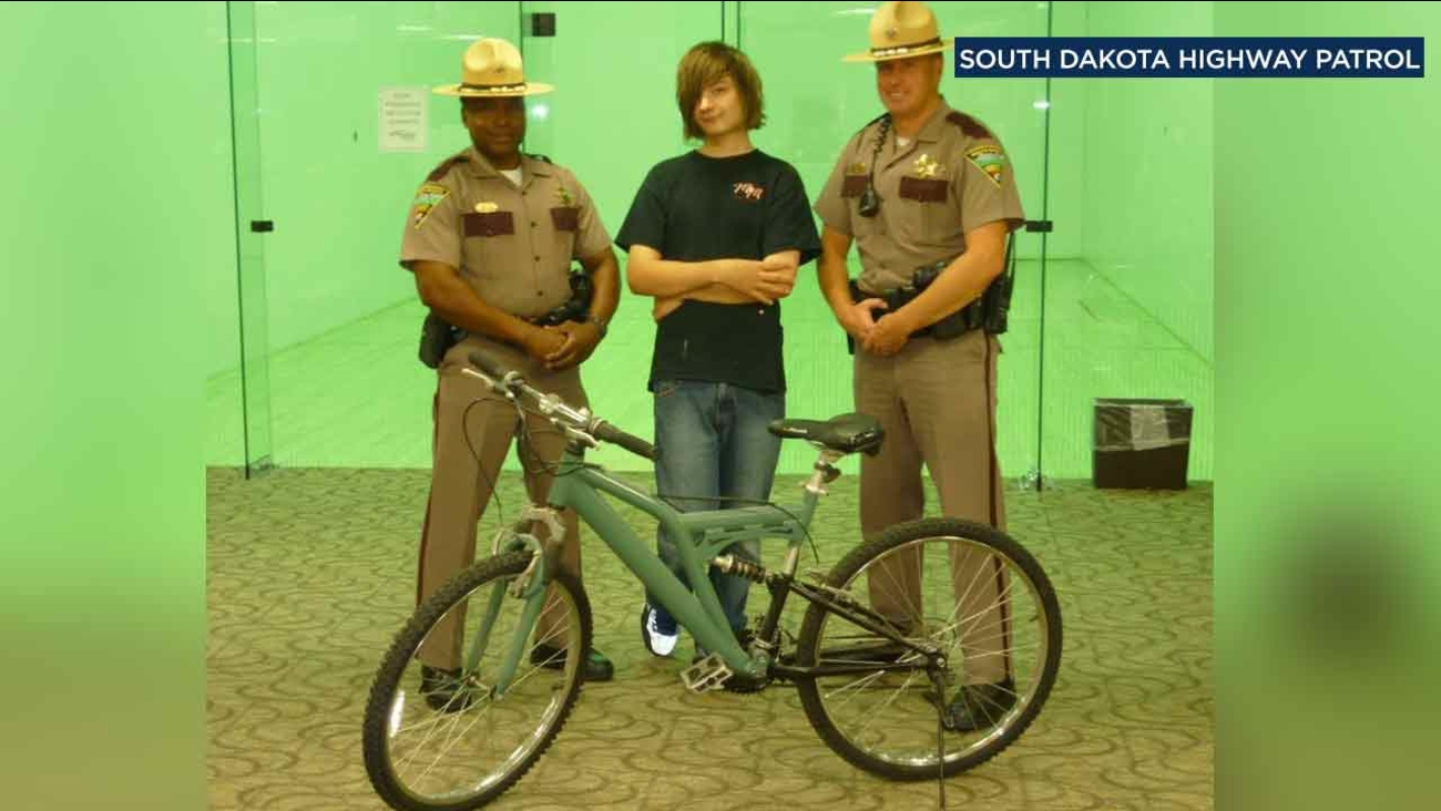 Two South Dakota Highway Patrol troopers pose with a teen, who walks eight miles to work, after buying him a bicycle.