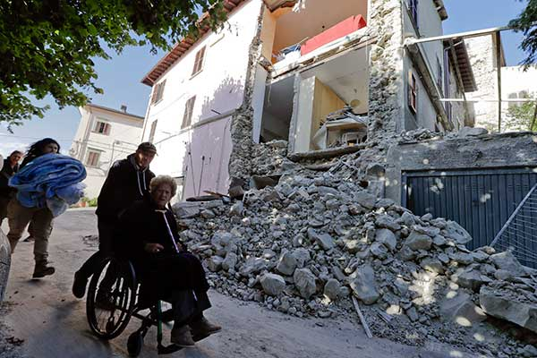 <div class='meta'><div class='origin-logo' data-origin='none'></div><span class='caption-text' data-credit='Andrew Medichini/AP Photo'>A woman on a wheelchair is pushed past a partially collapsed building is seen in the background following an earthquake, in Accumoli.</span></div>