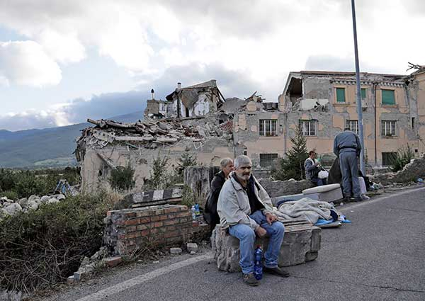 <div class='meta'><div class='origin-logo' data-origin='none'></div><span class='caption-text' data-credit='Alessandra Tarantino/AP Photo'>People sit on the side of a road as collapsed buildings are seen in the background following an earthquake, in Amatrice, Italy, Wednesday, Aug. 24, 2016.</span></div>