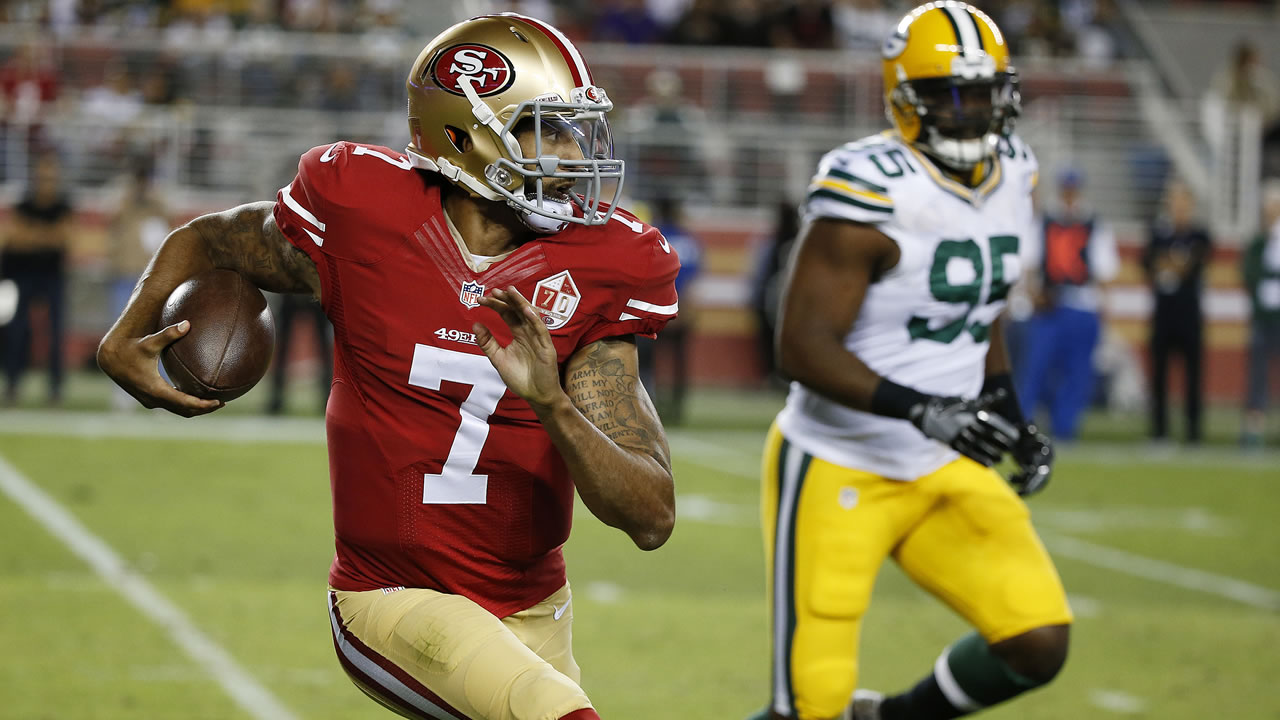 San Francisco 49ers quarterback Colin Kaepernick, left, runs with the ball as Green Bay Packers defensive end Datone Jones pursues during of an NFL preseason football game.