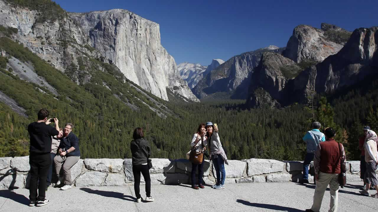 In this Oct. 17, 2013 file photo, visitors at Tunnel View enjoy the views of Yosemite National Park, Calif. (AP Photo/Gary Kazanjian, File)