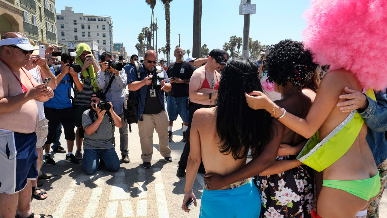 Topless women pose for photographers in Venice to demand that females get the same legal right as men to walk bare-chested in public on Sunday, Aug. 28, 2016.
