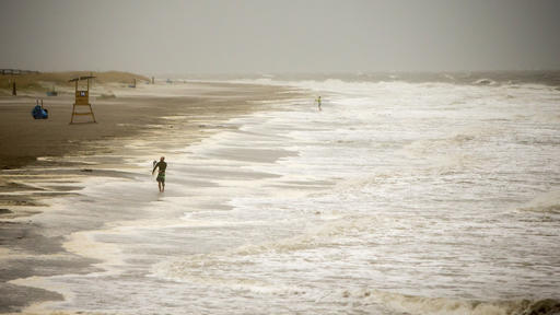 "<div class=""meta image-caption""><div class=""origin-logo origin-image none""><span>none</span></div><span class=""caption-text"">A surfer walks the beach while looking for waves from the surge of Hurricane Hermine off the coast of Tybee Island, Ga. (AP Photo/Stephen B. Morton)</span></div>"