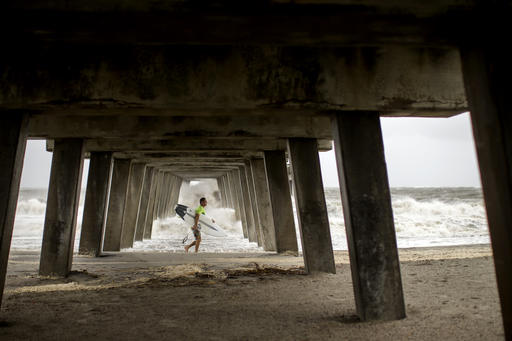 "<div class=""meta image-caption""><div class=""origin-logo origin-image none""><span>none</span></div><span class=""caption-text"">A surfer walks under a pier after surfing waves from the surge of Hurricane Hermineoff the coast of Tybee Island, Ga. (AP Photo/Stephen B. Morton)</span></div>"
