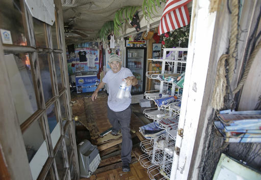 """<div class=""""meta image-caption""""><div class=""""origin-logo origin-image none""""><span>none</span></div><span class=""""caption-text"""">Gus Soldatos steps over a hole in the floor as  he brings water out of his son's bait shop after Hurricane Hermine Friday, Sept. 2, 2016, in Cedar Key, Fla. (AP)</span></div>"""