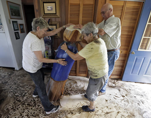 """<div class=""""meta image-caption""""><div class=""""origin-logo origin-image none""""><span>none</span></div><span class=""""caption-text"""">Harriet Oglesby, left, and her husband Hugh, right, help Bobbi Pattison stand up a sea captain statue carved out of wood from a 1993 storm  Friday, Sept. 2, in Steinhatchee, Fla. (AP)</span></div>"""