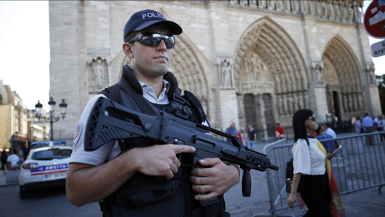 A French police officer patrols in front of Notre Dame cathedral, in Paris, Friday Sept. 9, 2016