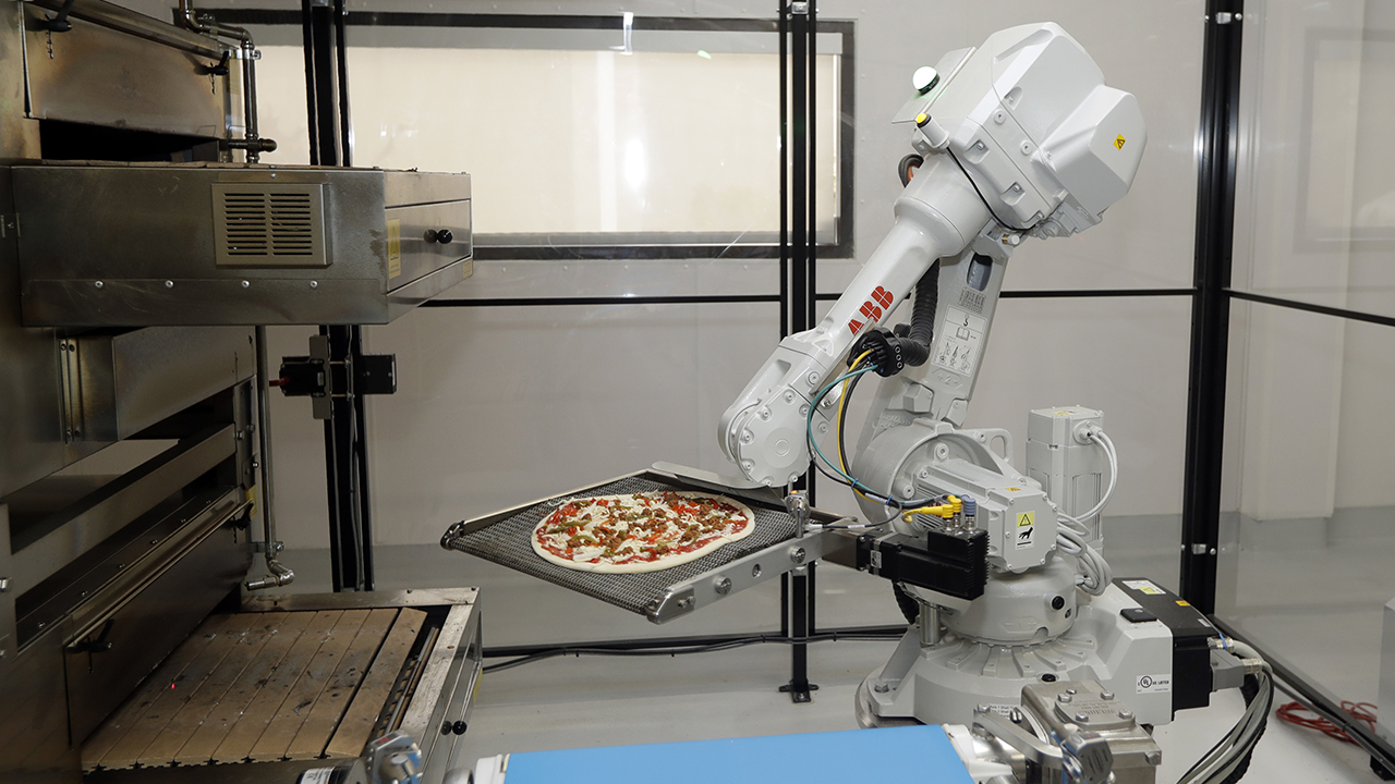 A robot places a pizza into an oven at Zume Pizza in Mountain View, California