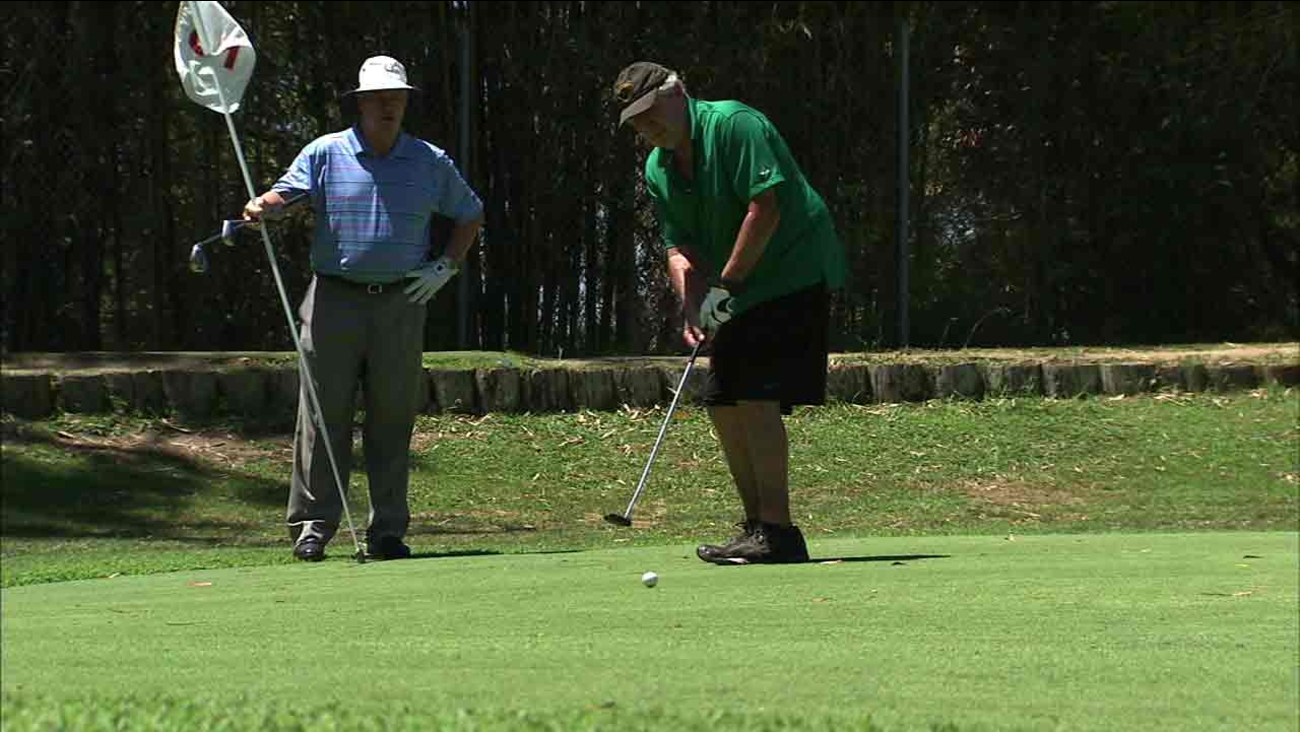 PGA Golf Pro Jim Dennerline looks on as Vietnam Veteran Will Tynan putts at the Heroes Golf Course.