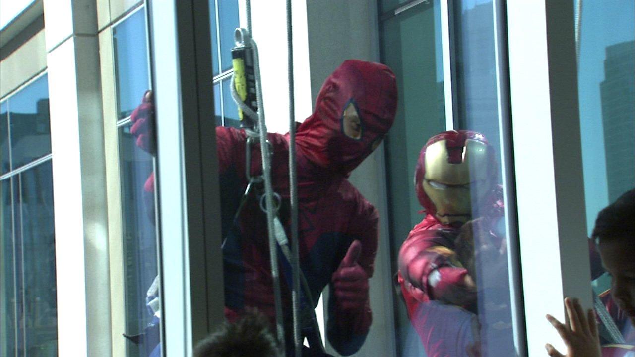Superheroes clean windows at children's hospital