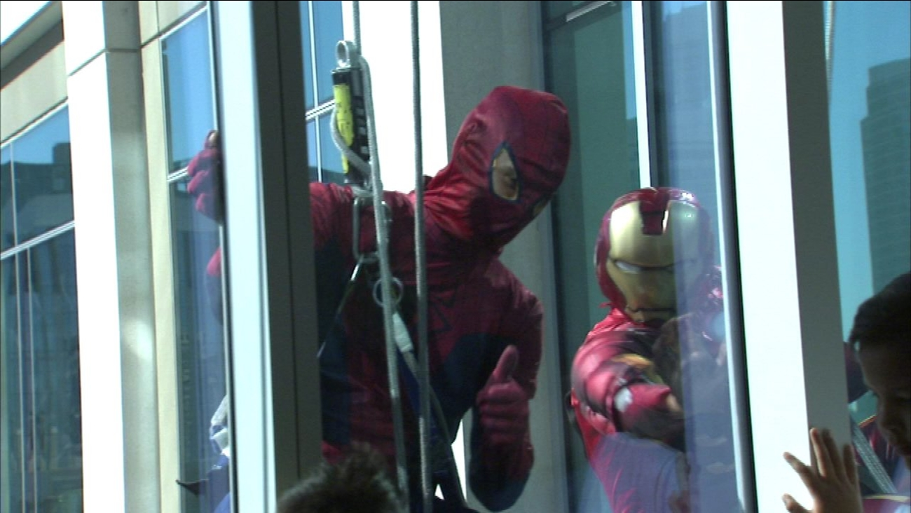 Superheroes clean windows at children's hospital