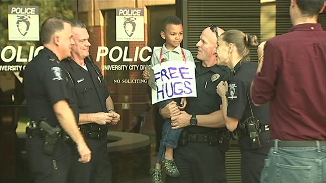 "This image shows five-year-old Jayden Hooker giving out ""free hugs"" to police officers in North Carolina."