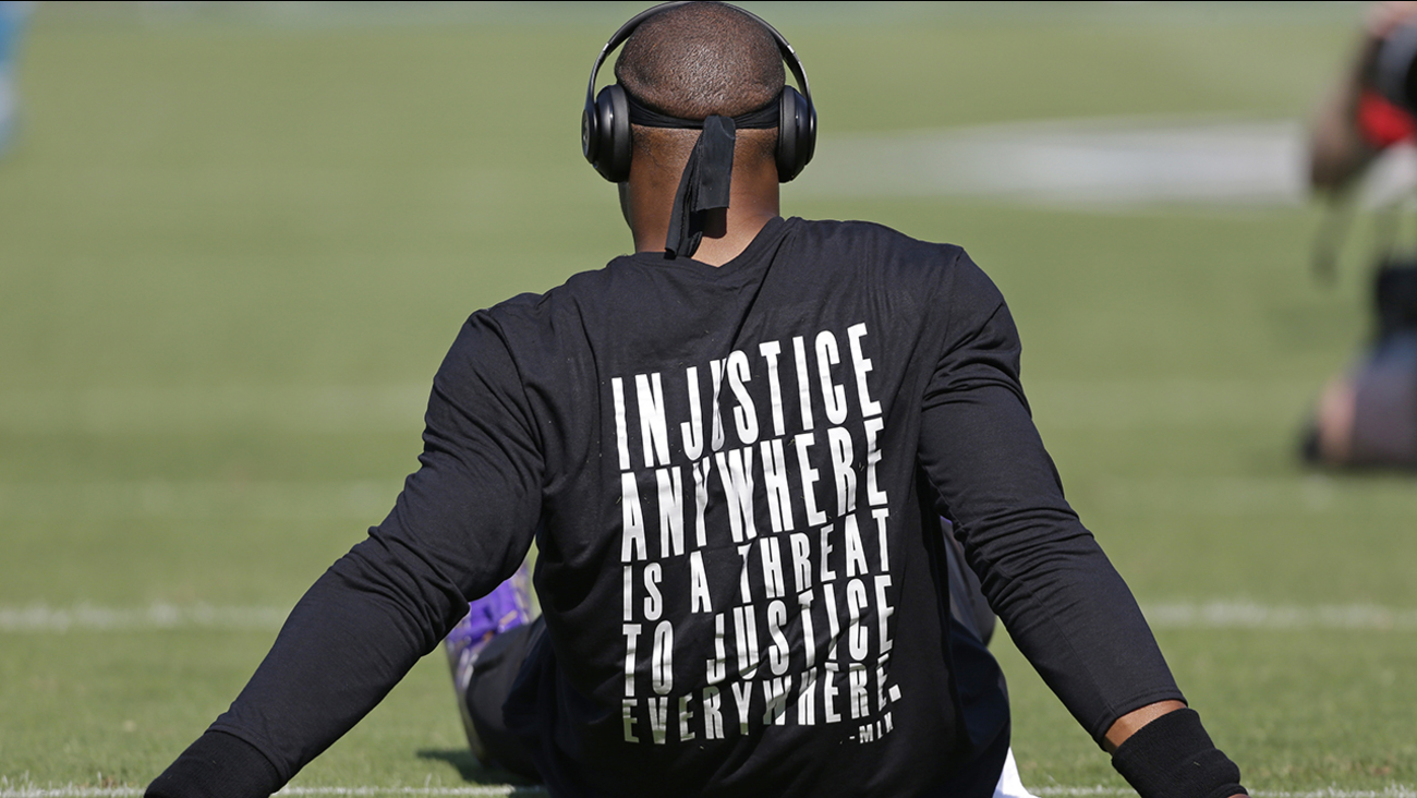Carolina Panthers' Cam Newton wears a shirt with a quote by Martin Luther King as he warms up before an NFL football game against the Minnesota Vikings in Charlotte, N.C.