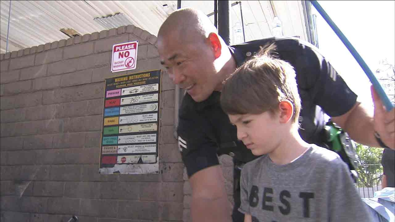 A Topanga Division police officer and Sebastian wash a car as part of the 6-year-old's fundraiser, held to help get the boy an autism service dog.