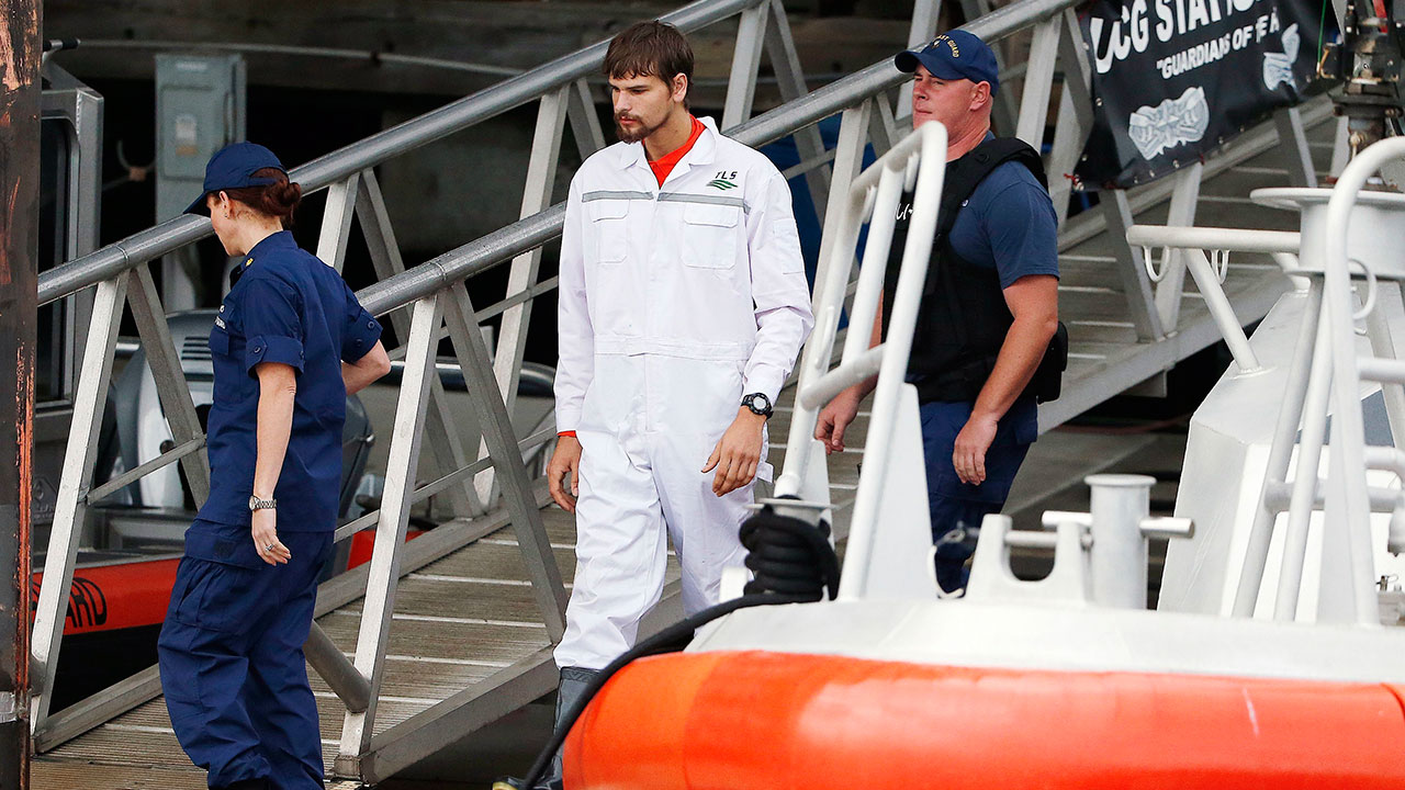 Nathan Carman, center, disembarks from a small boat at the US Coast Guard station in Boston, Tuesday, Sept. 27, 2016.