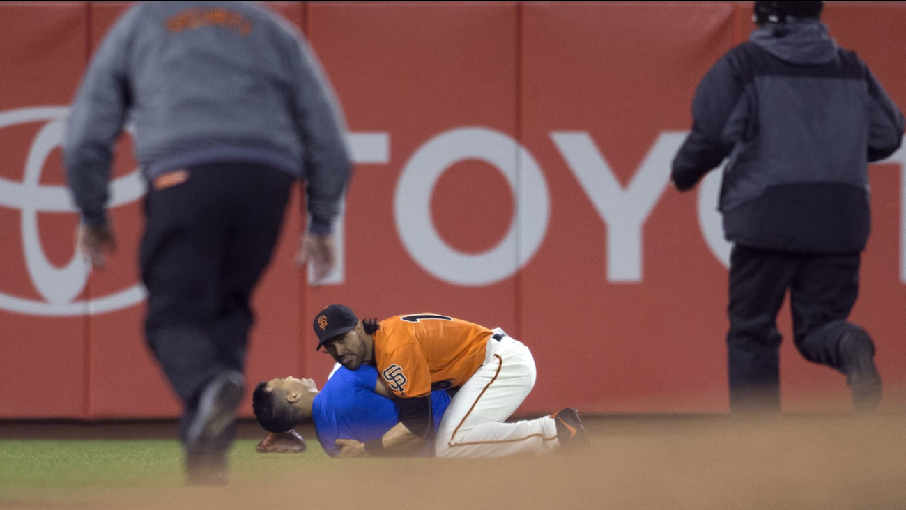 San Francisco Giants' Angel Pagan (16) holds down a man who ran onto the field during the Giants' baseball game against the Los Angeles Dodgers, Sept. 30, 2016 in San Francisco.
