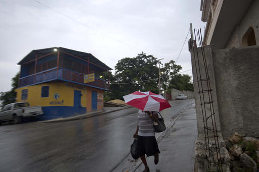 <div class='meta'><div class='origin-logo' data-origin='AP'></div><span class='caption-text' data-credit='Dieu Nalio Chery'>A woman walks with an umbrella as protection from a light rain, in Port-au-Prince, Haiti, Monday, Oct. 3, 2016.</span></div>