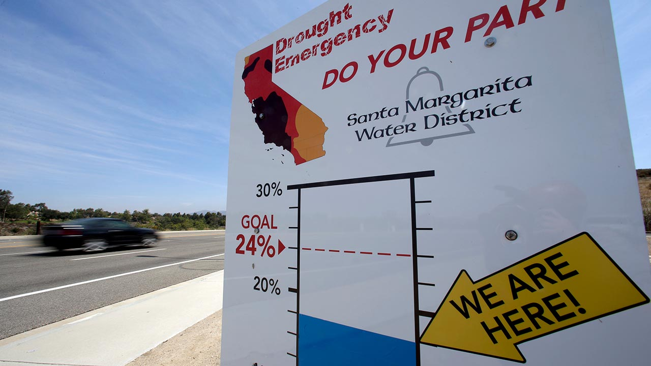 FILE - In this July 2, 2015, file photo, cars by a sign encouraging residents to save water in Rancho Santa Margarita.