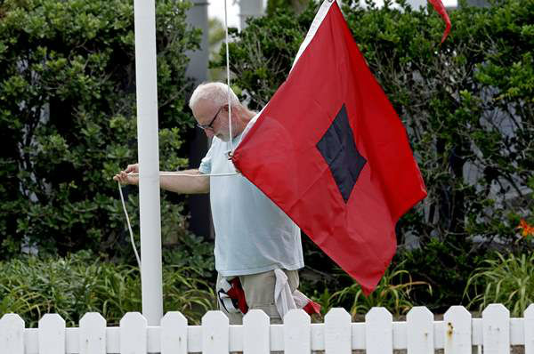 "<div class=""meta image-caption""><div class=""origin-logo origin-image ""><span></span></div><span class=""caption-text"">Bill Peters, innkeeper at the Cypress House Inn in Kill Devil Hills, N.C., prepares to raise a hurricane warning flag Thursday, July 3, 2014. (AP / Gerry Broome)</span></div>"