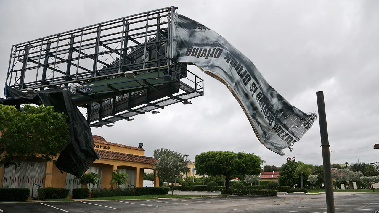 A billboard canvas flaps in the wind after Hurricane Matthew passed off shore, Friday, Oct. 7, 2016, in North Palm Beach, Fla.