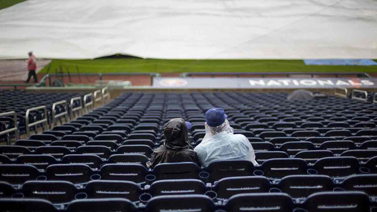 Fans take their seats in the rain before the start of Game 2 of the National League Division Series at Nationals Park between the Dodgers and Nationals Saturday, Oct. 8, 2016.